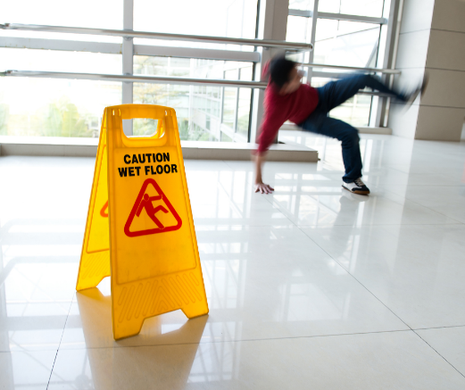A person falling to the floor with a caution wet floor sign placed.